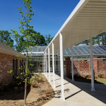white aluminum walkway canopy connecting two buildings on medical facility
