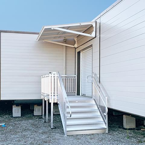 Folding metal canopy on a modular building in upright position