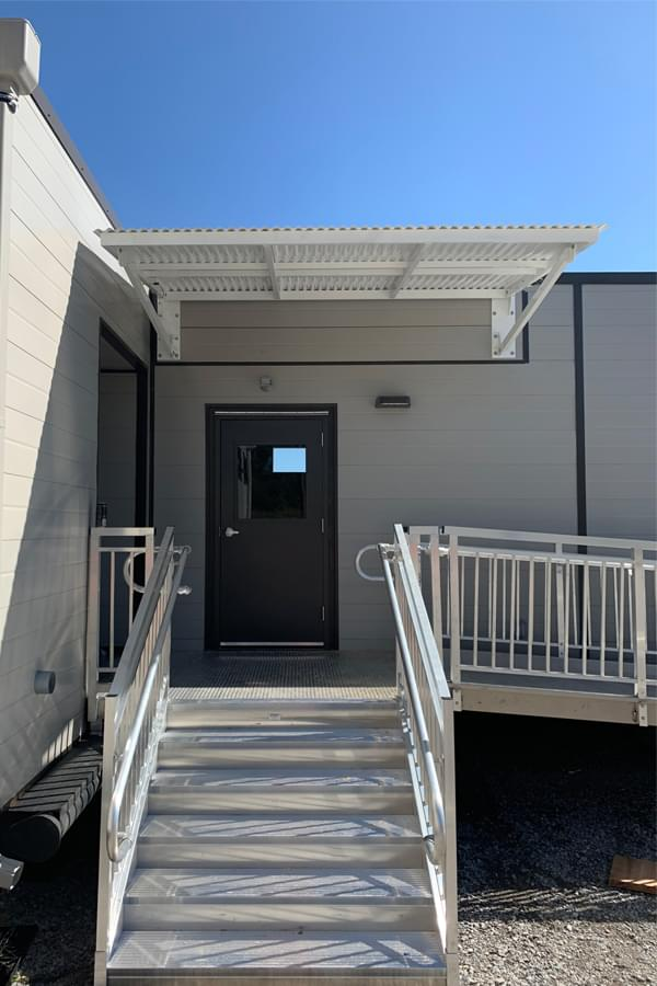 White folding aluminum canopy over a doorway on a modular building