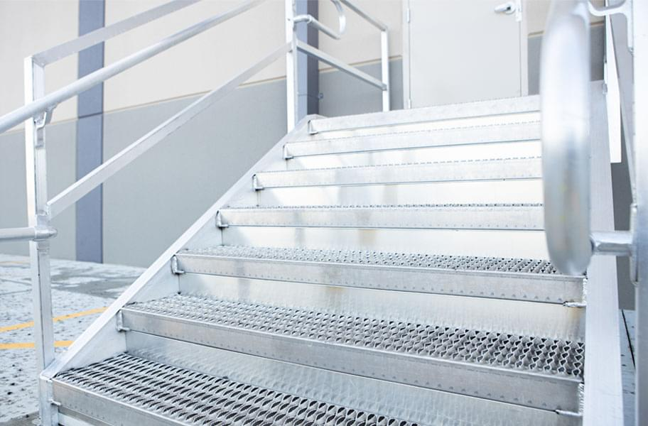 Loading dock stairs with grip strut step treads